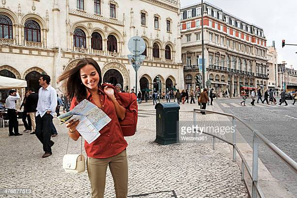 Portugal, Lisboa, Baixa, Rossio, smiling young woman with city map