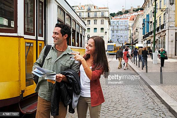 Portugal, Lisboa, Baixa, Rossio, young couple with city map in front of tram