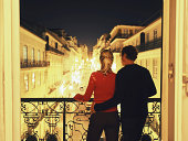 Portugal, Lisbon, couple on balcony above street at night, rear view