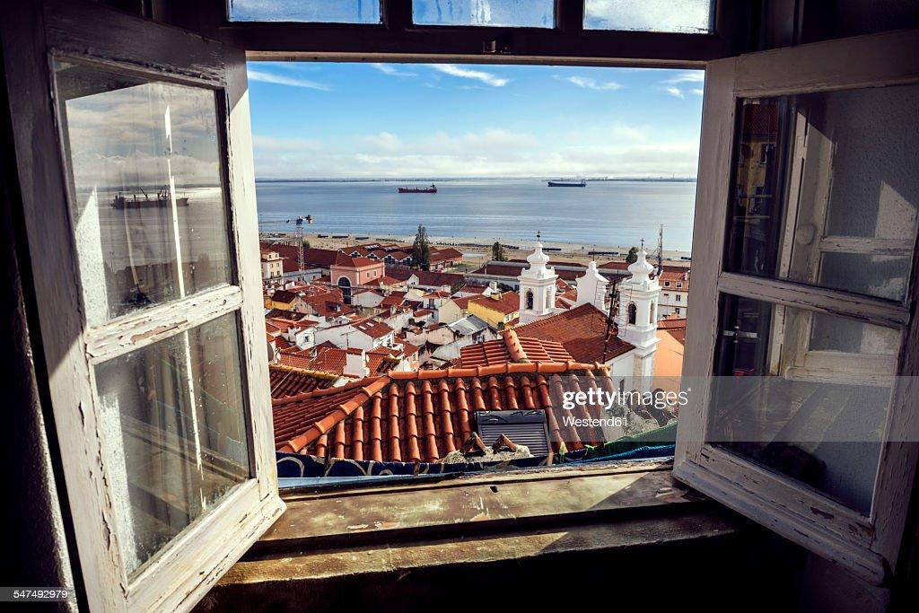 Portugal, Lisbon, view of Alfama neighborhood and River Tejo through open window