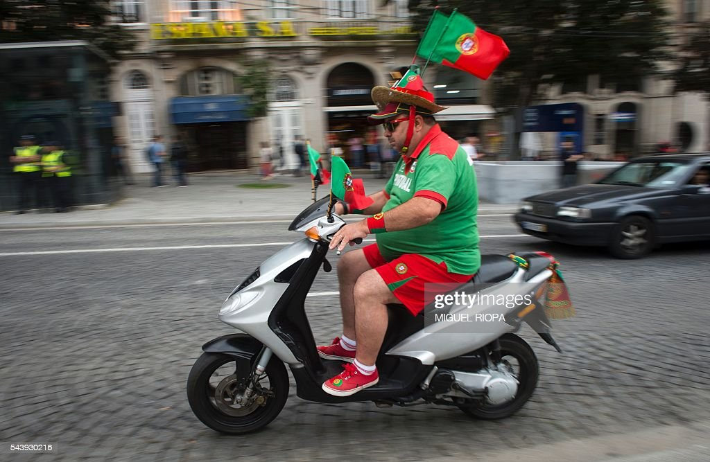 A Portugal national football team supporter with flags on his hat rides a scooter along Aliados Avenue in Porto on June 30, 2016, before the Euro 2016 football match between Portugal and Poland held at the Stade Velodrome in Marseille, France. / AFP / MIGUEL