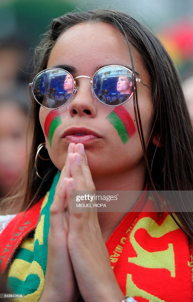 A Portugal national football team's supporter prays in Porto on June 30, 2016, before the Euro 2016 football match between Portugal and Poland held at the Stade Velodrome in Marseille, France. / AFP / MIGUEL