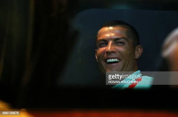 Portugal national team forward Cristiano Ronaldo smiles as he sits inside a bus upon the team arrival in Kazan late on June 14 to take part in the...