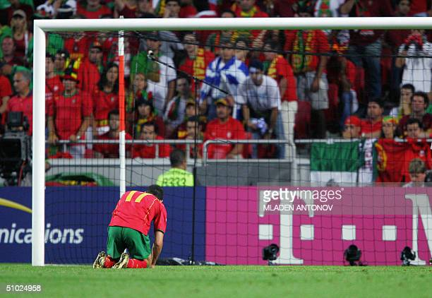 Portuguese forward Cristiano Ronaldo kneels on the ground 04 july 2004 at the Stadio Da Luz in Lisbon after the Euro 2004 final match between...