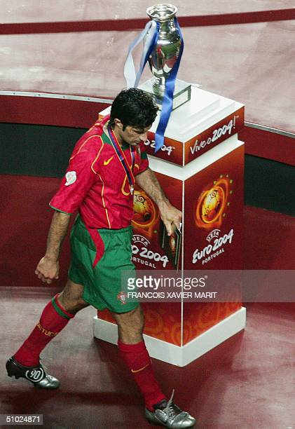 Portuguese midfielder Luis Figo walks by the cup 04 July 2004 at Stadio da Luz in Lisbon during the Euro 2004 final football match between Portugal...