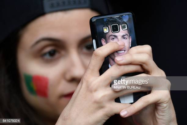 Portugal supporter uses her mobile device decorated with a picture of Portugal's forward Cristiano Ronaldo prior to the Euro 2016 group F football...