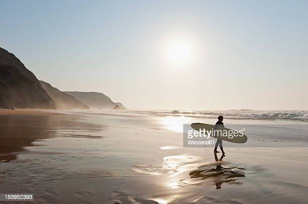 Portugal, Surfer walking on beach