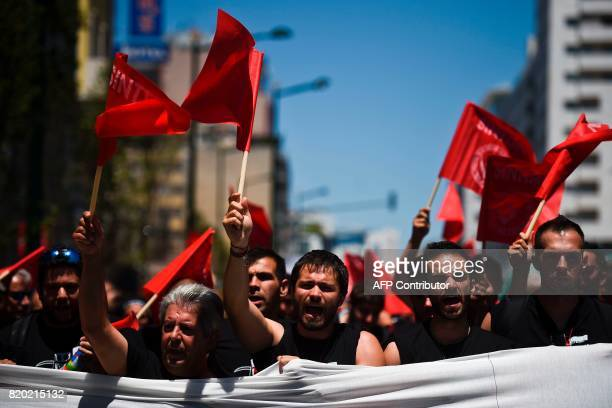 Portugal Telecom's workers wave flags and shout slogans as they gather in front of the company's headquarters during a 24 hours strike to protest...