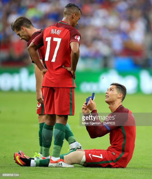 Portugal's Cristiano Ronaldo passes the captain's armband to teammate Nani after picking up an injury early in the game