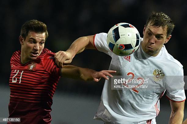 Portugal's defender Cedric vies for the ball with Russia's forward Artem Dzyuba during the friendly football match between Russia and Portugal in...