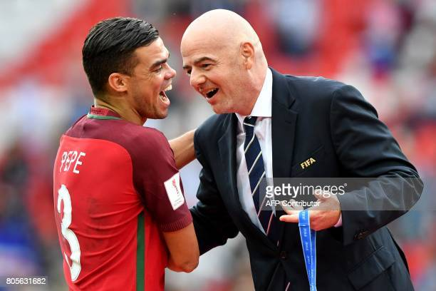 TOPSHOT Portugal's defender Pepe is congratulated by FIFA president Gianni Infantino before receiving his bronze medal at the end of the 2017 FIFA...