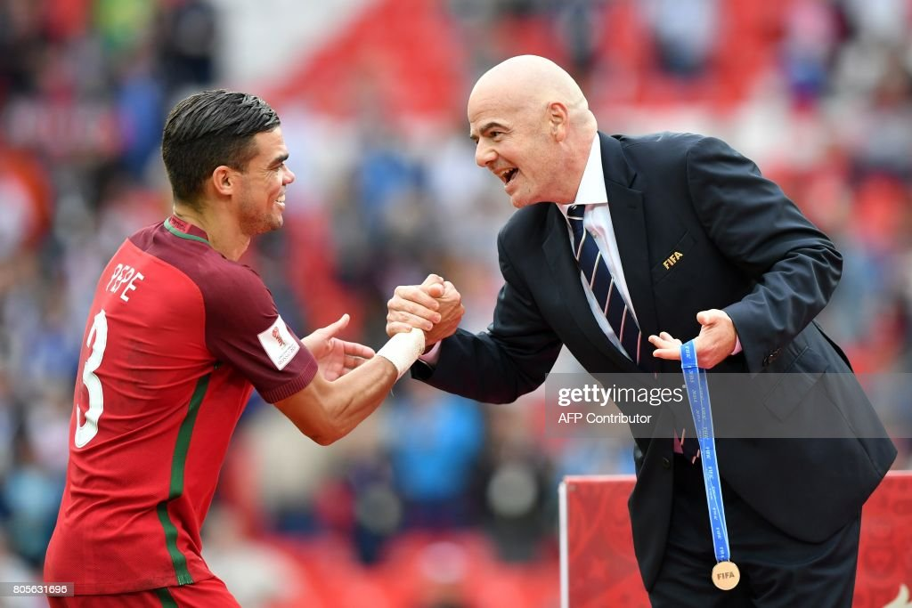 Portugal's defender Pepe is congratulated by FIFA president Gianni Infantino (R) before receiving his bronze medal at the end of the 2017 FIFA Confederations Cup third place football match between Portugal and Mexico at the Spartak Stadium in Moscow on July 2, 2017. / AFP PHOTO / Yuri KADOBNOV