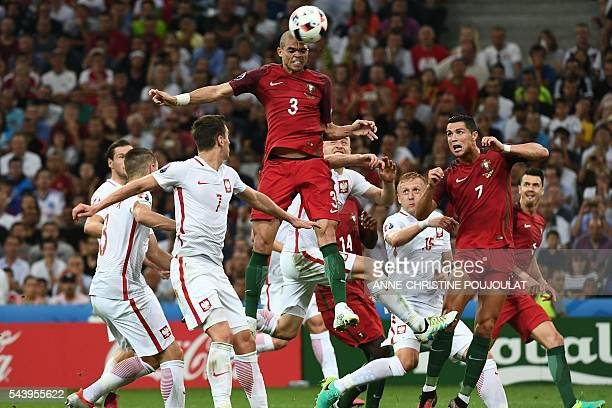 TOPSHOT Portugal's defender Pepe jumps for the ball next to Poland's forward Arkadiusz Milik during the Euro 2016 quarterfinal football match between...