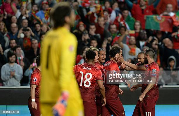 Portugal's defender Ricardo Carvalho celebrates with teammates after scoring the opening goal during the Portugal vs Serbia EURO 2016 qualifying...