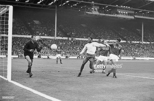 Portugal's Eusebio forces his way between two Russian players only to see his shot saved by Russian goalkeeper Lev Yashin during the World Cup match...