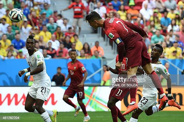 Portugal's forward and captain Cristiano Ronaldo heads the ball towards the goal as Ghana's defender John Boye watches on during to the Group G...