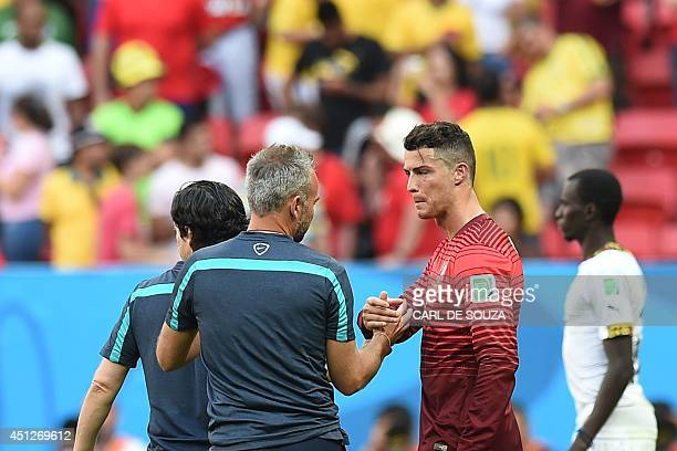 Portugal's forward and captain Cristiano Ronaldo shakes hands with a member of the Portugal training squad at the end of the Group G football match...