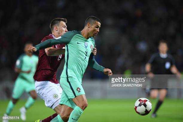 Portugal's forward Cristiano Ronaldo and Latvia's Vitalijs Jagodinskis vie for the ball during the FIFA World Cup 2018 qualification football match...
