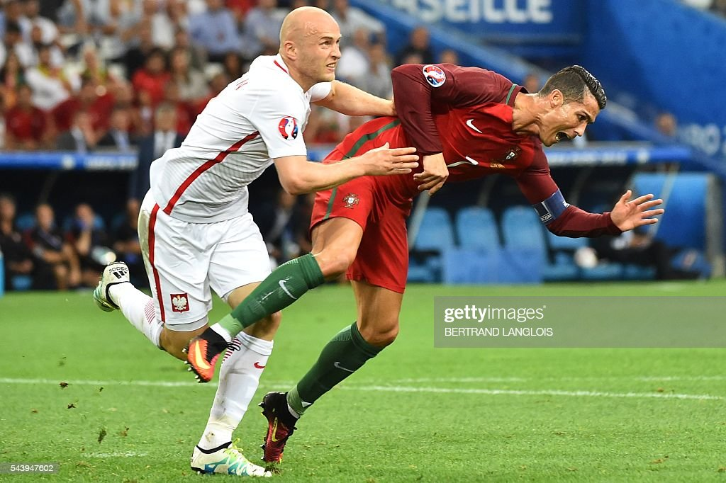 TOPSHOT - Portugal's forward Cristiano Ronaldo (R) and Poland's defender Michal Pazdan fall during the Euro 2016 quarter-final football match between Poland and Portugal at the Stade Velodrome in Marseille on June 30, 2016. / AFP / BERTRAND