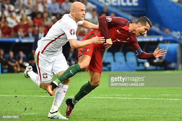 TOPSHOT Portugal's forward Cristiano Ronaldo and Poland's defender Michal Pazdan fall during the Euro 2016 quarterfinal football match between Poland...