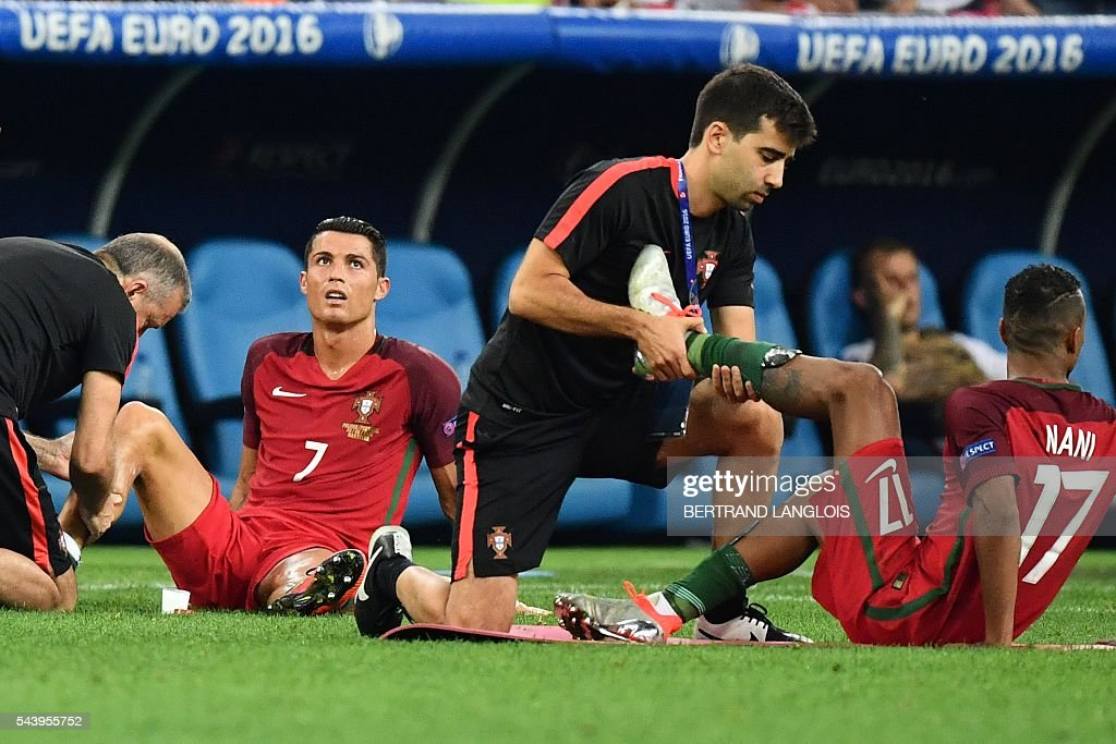 Portugal's forward Cristiano Ronaldo (2L) and Portugal's forward Nani (R) receive leg massages prior to overtime during the Euro 2016 quarter-final football match between Poland and Portugal at the Stade Velodrome in Marseille on June 30, 2016. / AFP / BERTRAND