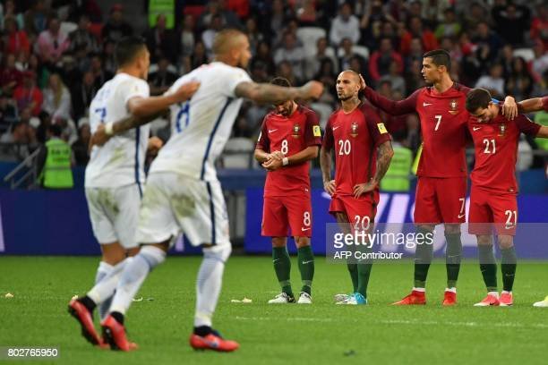 Portugal's forward Cristiano Ronaldo and team mates react as Chile's players celebrate after the 2017 Confederations Cup semifinal football match...