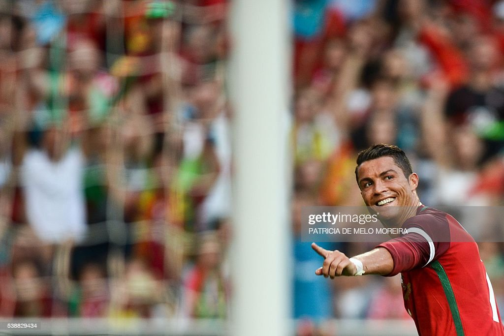TOPSHOT - Portugal's forward <a gi-track='captionPersonalityLinkClicked' href=/galleries/search?phrase=Cristiano+Ronaldo+-+Soccer+Player&family=editorial&specificpeople=162689 ng-click='$event.stopPropagation()'>Cristiano Ronaldo</a> celebrates after scored against Estonia during the friendly football match Portugal vs Estonia at Luz stadium in Lisbon on June 8, 2016, in preparation for the upcoming UEFA Euro 2016 Championship. / AFP / PATRICIA