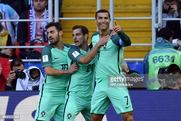 Portugal's forward Cristiano Ronaldo celebrates with Portugal's defender Cedric and Portugal's midfielder Bernardo Silva after scoring during the...