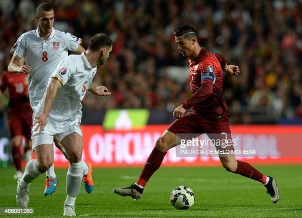 Portugal's forward Cristiano Ronaldo controls the ball near Serbian defender Branislav Ivanovic and midfielder Aleksandar Mitrovic during the...