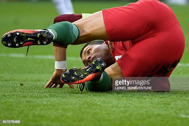 TOPSHOT Portugal's forward Cristiano Ronaldo falls on the pitch during the Euro 2016 group F football match between Portugal and Austria at the Parc...
