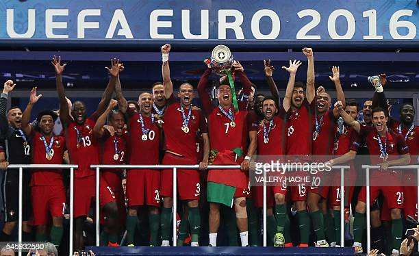 Portugal's forward Cristiano Ronaldo flanked by his teammates poses with the trophy after Portugal beat France during the Euro 2016 final football...
