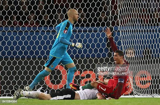 TOPSHOT Portugal's forward Cristiano Ronaldo gestures demanding a penalty to referee beside Austria's goalkeeper Robert Almer during the Euro 2016...