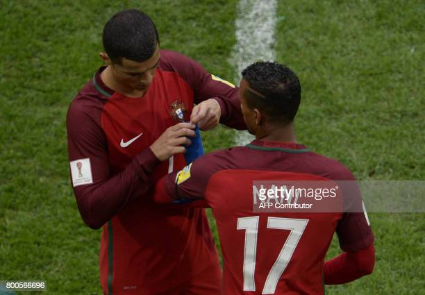 Portugal's forward Cristiano Ronaldo gives his captain armband to Portugal's forward Nani as he leaves the pitch after being substituted during the...