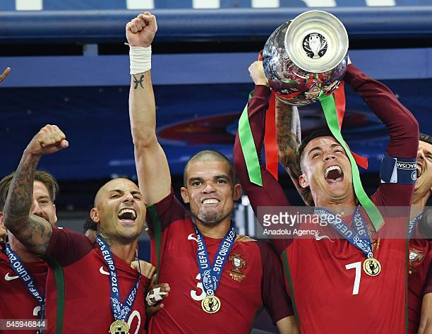 Portugal's forward Cristiano Ronaldo hold up the winners' trophy as he celebrates with teammates Portugal's forward Ricardo Quaresma Portugal's...
