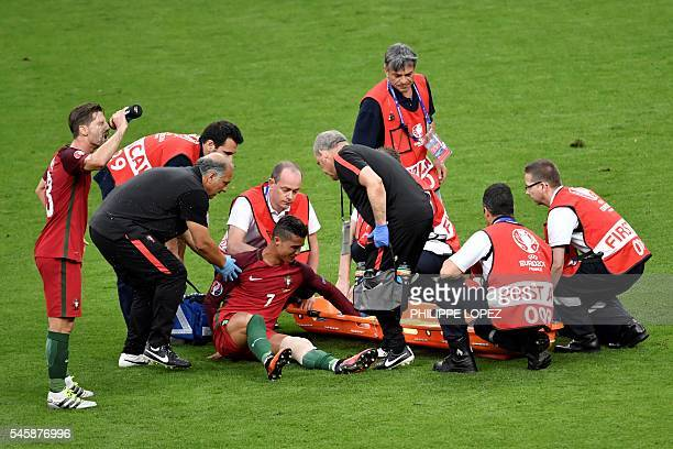 TOPSHOT Portugal's forward Cristiano Ronaldo is lifted onto a stretcher by medics after an injury following a clash with France's forward Dimitri...