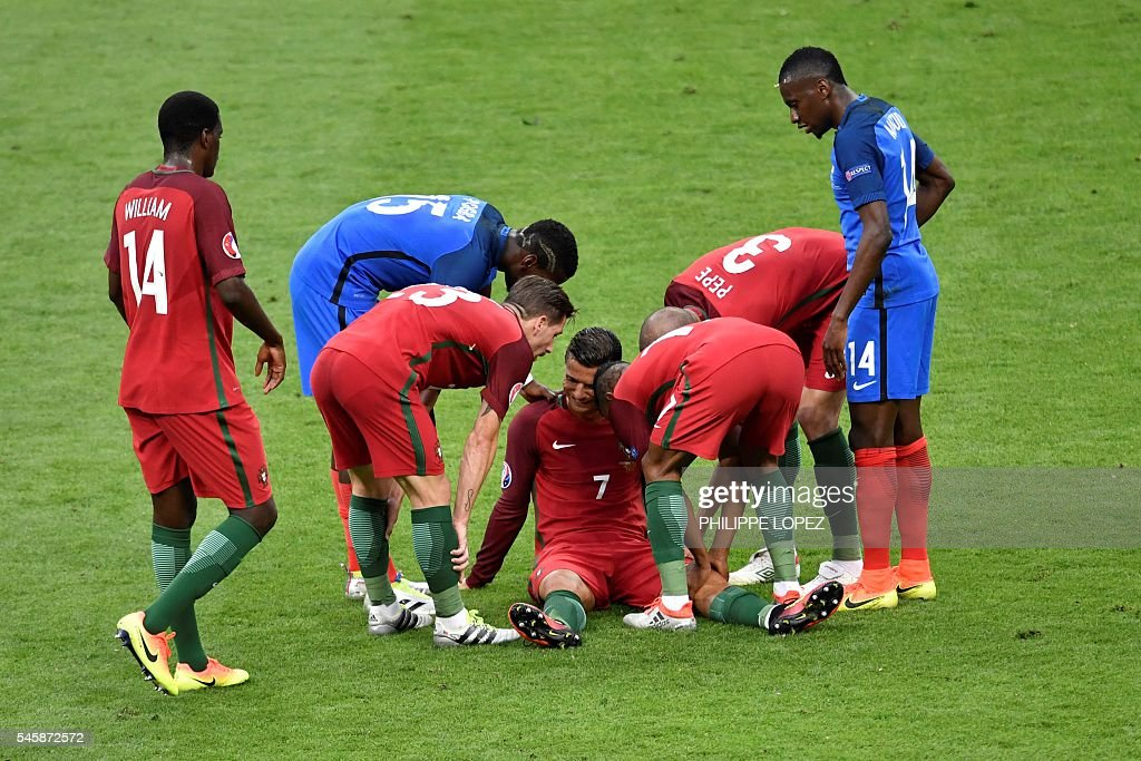 TOPSHOT - Portugal's forward Cristiano Ronaldo (C) is surrounded by team mates and France's midfielder Paul Pogba (2L) and France's midfielder Blaise Matuidi (R) as he reacts after an injury following a clash with France's forward Dimitri Payet (not pictured) during the Euro 2016 final football match between Portugal and France at the Stade de France in Saint-Denis, north of Paris, on July 10, 2016. / AFP / PHILIPPE