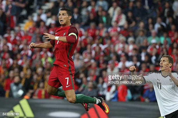 TOPSHOT Portugal's forward Cristiano Ronaldo jumps for the ball as Austria's defender Florian Klein looks at him during the Euro 2016 group F...