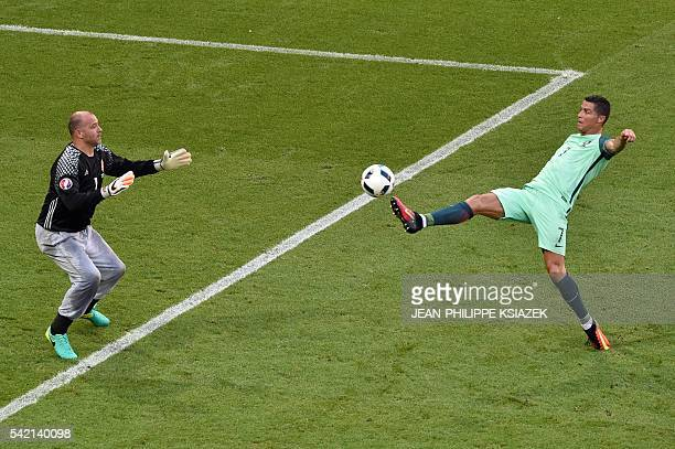 TOPSHOT Portugal's forward Cristiano Ronaldo kicks the ball in front of Hungary's goalkeeper Gabor Kiraly during the Euro 2016 group F football match...