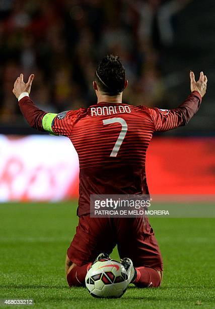 Portugal's forward Cristiano Ronaldo kneels on the field during the Portugal vs Serbia EURO 2016 qualifying football match at Luz stadium in Lisbon...
