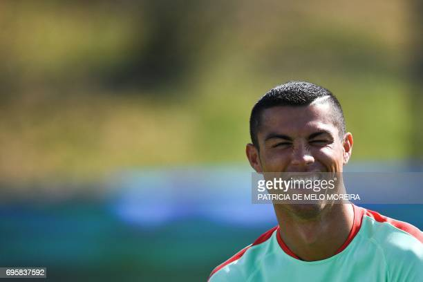 Portugal's forward Cristiano Ronaldo laughs during a training session at 'Cidade do Futebol' training camp in Oeiras outskirts of Lisbon on June 14...