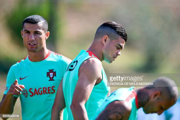 Portugal's forward Cristiano Ronaldo looks on past Portugal's defender Pepe during a training session at 'Cidade do Futebol' training camp in Oeiras...
