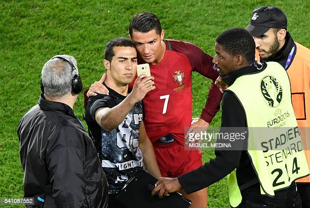 Portugal's forward Cristiano Ronaldo poses for a picture with a supporter who entered the pitch after the Euro 2016 group F football match between...
