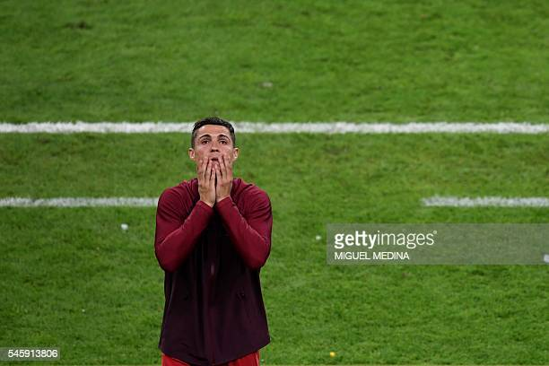 TOPSHOT Portugal's forward Cristiano Ronaldo reacts during the Euro 2016 final football match between Portugal and France at the Stade de France in...