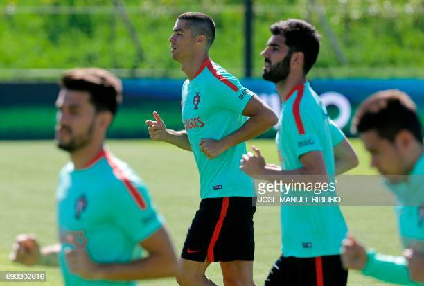 Portugal's forward Cristiano Ronaldo runs with his team mates during a training session at 'Cidade do Futebol' training camp in Oeiras outskirts of...