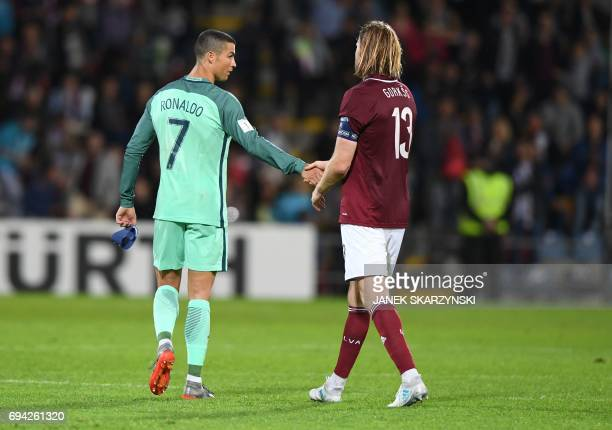 Portugal's forward Cristiano Ronaldo shakes hands with Latvia's Kaspars Gorkss after the FIFA World Cup 2018 qualification football match between...