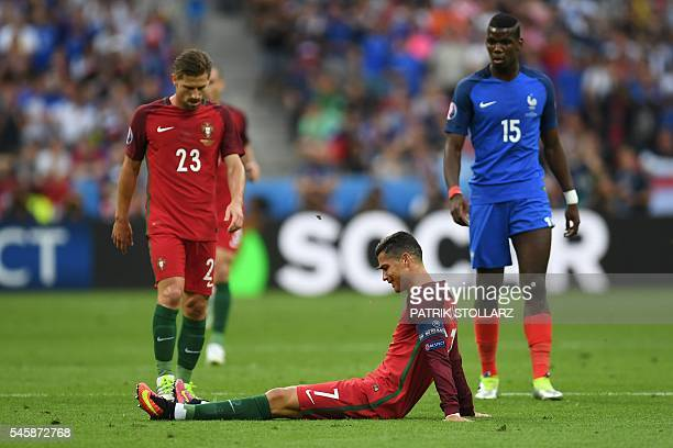 TOPSHOT Portugal's forward Cristiano Ronaldo sits injured on the pitch during the Euro 2016 final football match between Portugal and France at the...