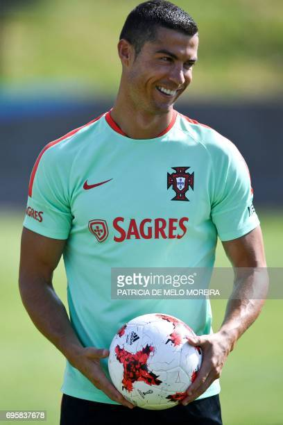 Portugal's forward Cristiano Ronaldo smiles as he holds a ball during a training session at 'Cidade do Futebol' training camp in Oeiras outskirts of...