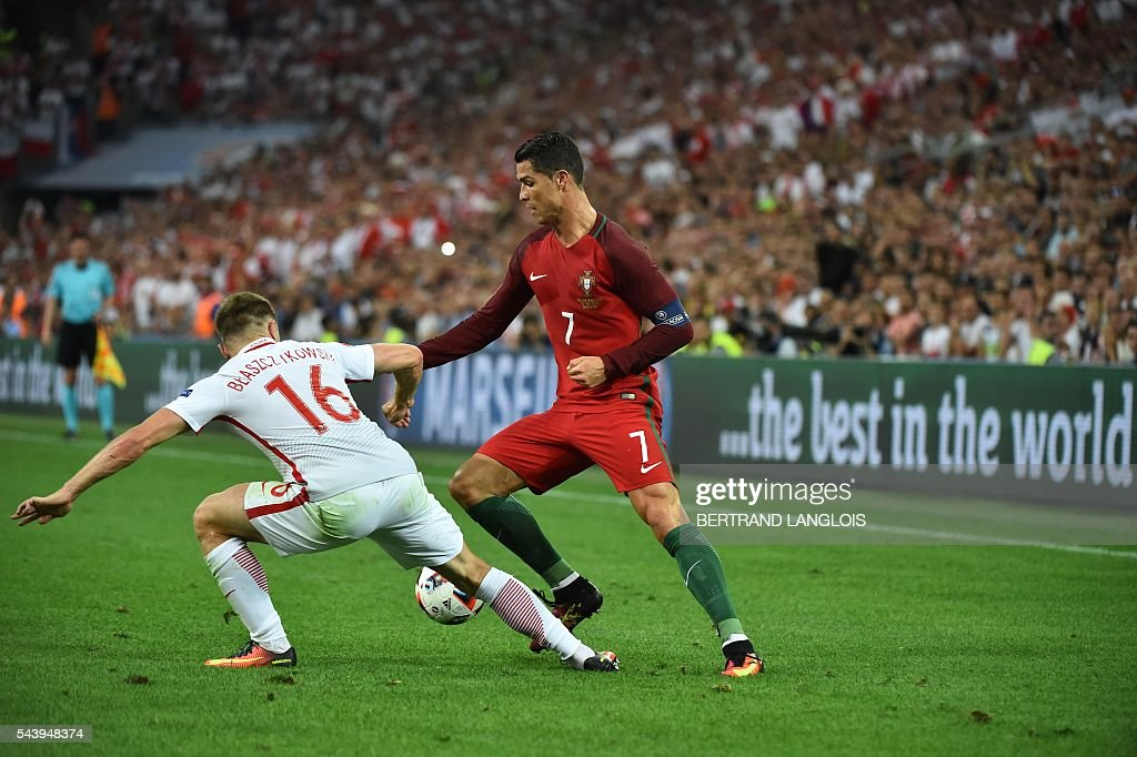 Portugal's forward Cristiano Ronaldo vies for the ball with Poland's midfielder Jakub Blaszczykowski during the Euro 2016 quarter-final football match between Poland and Portugal at the Stade Velodrome in Marseille on June 30, 2016. / AFP / BERTRAND