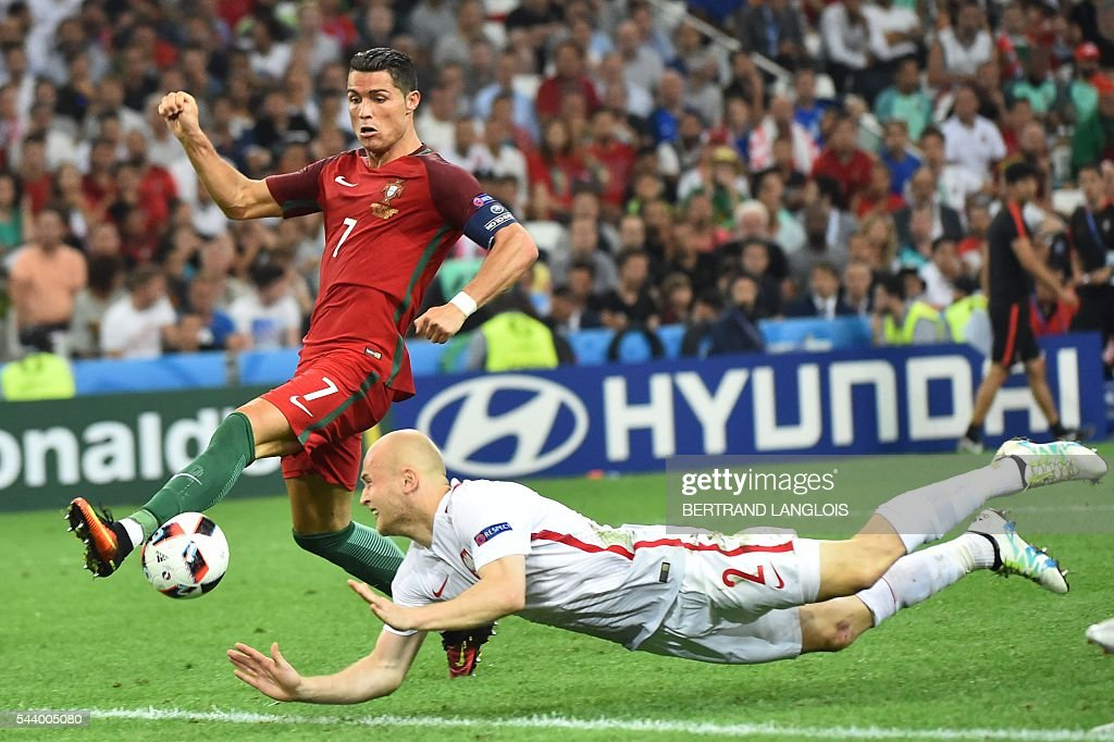 Portugal's forward Cristiano Ronaldo (L) vies for the ball with Poland's defender Michal Pazdan during the Euro 2016 quarter-final football match between Poland and Portugal at the Stade Velodrome in Marseille on June 30, 2016. / AFP / BERTRAND