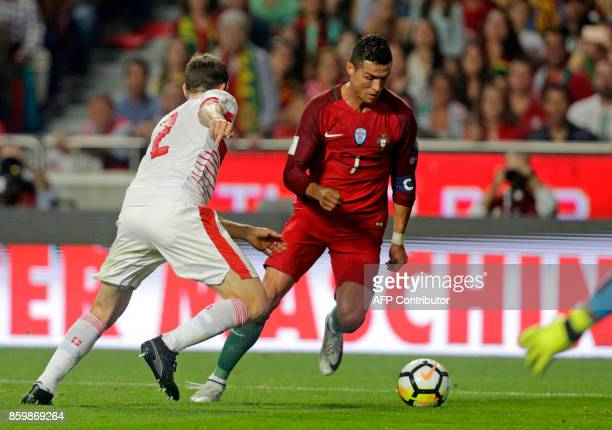 Portugals forward Cristiano Ronaldo vies with and Swiss defender Stephan Lichtsteiner during the FIFA World Cup 2018 Group B qualifier football match...